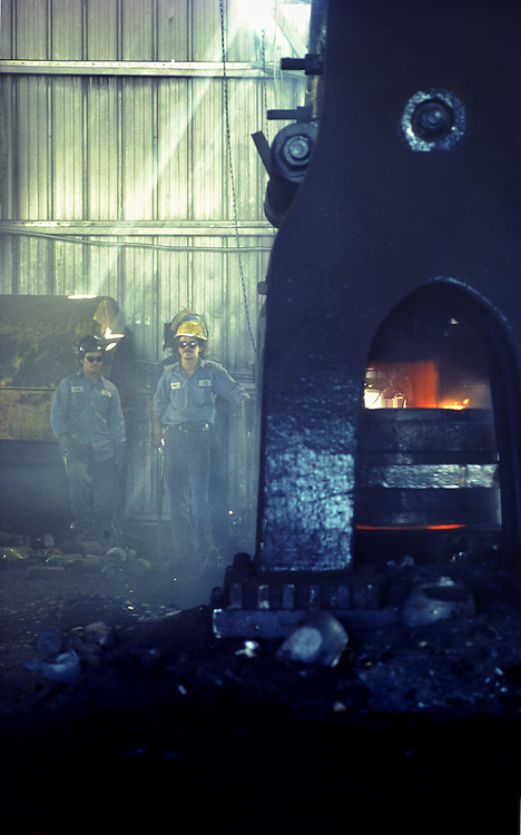 Two plant workers with work uniforms and hard hats forging steel in Houston, Texas. A large black furnace has flames burning inside with piles of ash piled up just outside the opening,