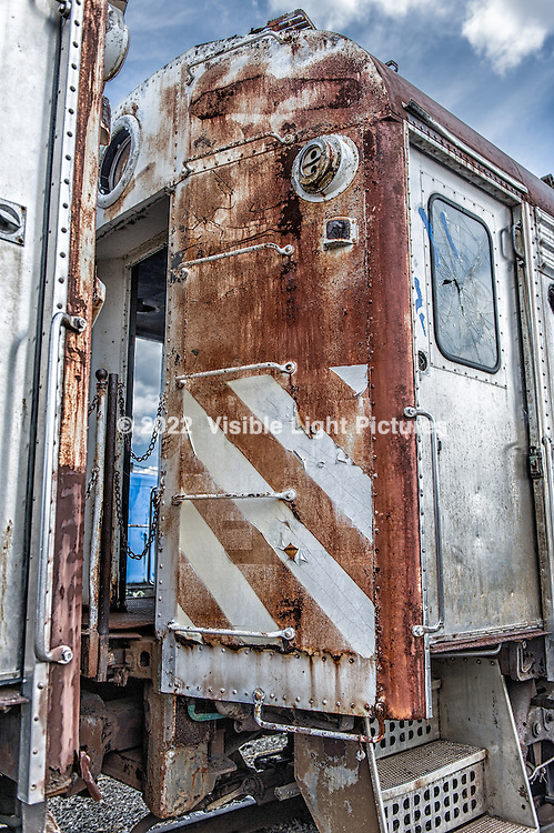 Rusted rail car with peeling safety stripes