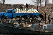North Koreans load a truck in the bank of the Yalu river in Sinuiju, North Korea, on Wednesday, Feb.  9, 2007. As The Six Party talks resume in Beijing the US envoy is ompimistic on North Korean nuclear talks.
