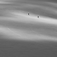 Two climbers cross the Vowell Glacier headed to Pigeon Spire, Bugaboo Provincial Park, British Columbia, Canada