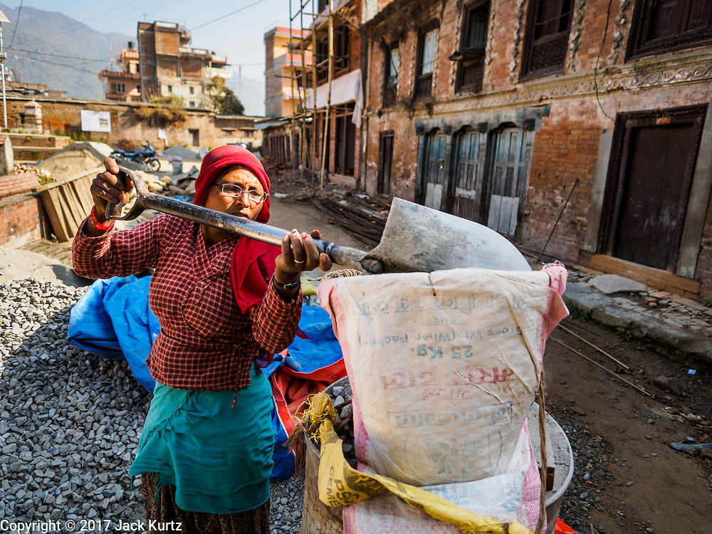 02 MARCH 2017 - SANKHU, NEPAL: A laborer fills a basket with gravel for a home being rebuilt in Sankhu after the 2015 earthquake. The building on the right is a 300 year old home that is no longer usable and will be torn down. There is more construction and rebuilding going on in Sankhu, west of central Kathmandu, than in many other parts of the Kathmandu Valley nearly two years after the earthquake of 25 April 2015 that devastated Nepal. In some villages in the Kathmandu valley workers are working by hand to remove ruble and dig out destroyed buildings. About 9,000 people were killed and another 22,000 injured by the earthquake. The epicenter of the earthquake was east of the Gorka district.   PHOTO BY JACK KURTZ