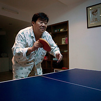 BEIJING, 25. JANUARY, 2009 :   Mr. Li, a paper factory owner, plays table tennis  on new year's eve in his apartment while his relatives entertain themselves  <br /> in his karaoke lounge or elsewhere.   <br /> Mr. Li, a paper factory owner, is facing one of his most difficult times .&quot; Last November the market suddenly went down ,&quot; Li says.   <br /> He had bought paper, a lot of paper, and paid 7000 Yuan/ t .<br />  Li's company buys paper from paper mills and lives from the sales to publishing houses and other companies.  Since the market's collapse , he manages to sell the paper only for 6000 Yuan/t.<br /> His clients' export business to the USA had shrunk in Southern China. Mobile phone manufacturers don't need paper for the instruction guides to their mobile phones anymore as their US clients buys less China- made mobile phones.<br />  Toy manufacturers don't need paper anymore  because Americans import less toys from China. &quot; The crisis has driven many of my clients into bancruptsy&quot;, says Li.<br />  <br /> China's Communist Party  which will celebrate its 60th anniversary in October, currently faces its biggest challenge since the beginning of the economic reforms 30 years ago  : &quot; The phase of  rapid economic growth is over. For the first time the government is threatened with a  mistrust of a wide section of the population&quot;, warns the Communist party's Shang Dewen in Beijing.   <br /> Not only the China's poorest worry about the furture, but as well China's middle class is concerned about the crisis.     1,5 Millionen university graduates didn't find a job until the end of 2008  and this summer there'll be an additional  6,1 Million new graduates. More than 12 percent of university graduates face unemployment in 2009.