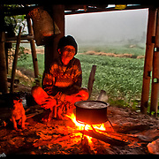 A Burmese refugee worker seeks warmth from a camp fire along the Thai-Cambodia border.