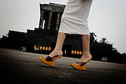 Hanoi. A young girl who is wear a new fashion shoes walking in front of the Ho Chi Minh mausoleum .