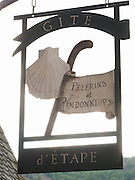 There are many small guest houses in the World Heritage village of Conques. This sign was welcoming pilgrims and walkers and features the traditional symbols of walking staff and Saint James scallop shell.