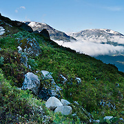 Above the village of Loen on Innvikfjorden arm of Nordfjord, ascend Skåla, the highest tidewater mountain in Norway. Between Tjugen camping and Loenvatnet, park at the pay lot and ascend to Skålatårnet (Skåla Tower, a DNT lodge) steeply on a well marked trail. Stepping stones greatly improve footing on the upper portion protected within Jostedalsbreen National Park (nasjonalpark). Hike 5 hours up and 3 hours down on a strenuous ascent of over 1800 meters (6000 feet). Loen is in Stryn municipality, Sogn og Fjordane county, Norway. Panorama stitched from 3 overlapping photos.