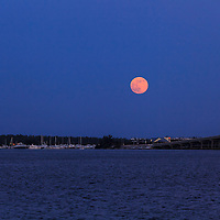 The full moon rises over Virginia Key and the William Powell Bridge in Biscayne Bay at Miami.