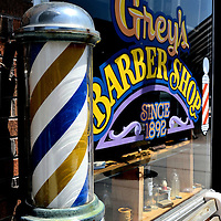 Spinning Barber Shop Pole at Grey's Barber Shop in Hayward, Wisconsin<br /> During medieval times, barbers were full service: they cut hair, performed surgery, blood let to cure diseases and extracted teeth. The red, white and blue pole represents these skills. Through the 1960s, the spinning barber pole was an iconic symbol. Today, in small towns like Hayward, Wisconsin, it is s a quaint storefront reminder of a bygone era. Grey&rsquo;s claims to have been cutting hair for over 120 years.