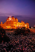 The Royal Palace in Msyore, otherwise known as the Amba Vilas Palace, lit up at night with flower blooming in front.