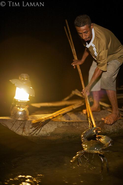 A fisherman spears a mangrove crab in Mayalibit Bay, Waigeo Island.