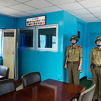 Two KPA soldiers standing guard inside a JSA conference room, in front of the door leading to the South Korean side of the JSA. View from north to south. This Image was deleted when crossing the DMZ, but could be restored afterwards.