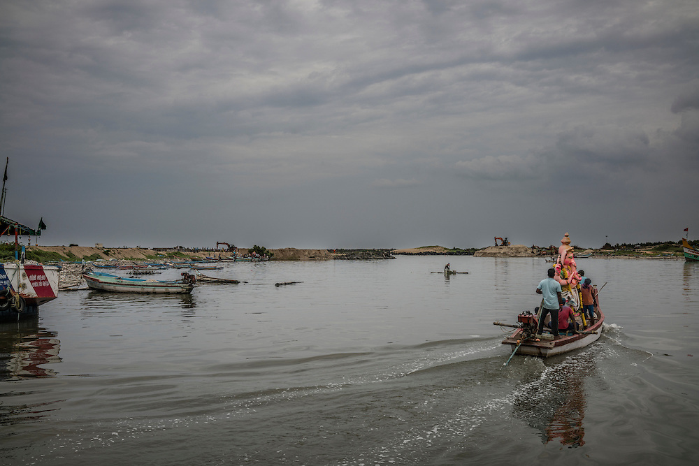 Men lead a boat loaded with a Lord Ganesha statue out of the Pondicherry fishing port to the open sea to send the statue symbolically back to nature as part of the Ganesh Chaturthi Festival.  Pondicherry, India.