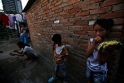 A picture made available on 30 July 2013 of Chinese children eating fruits in a slum or shanty town area by the second ring road of Beijing, metres away from the prosperous Central Business District (CBD), separated only by a busy highway in China, 29 July 2013. Beijing announced plans to spend 500 billion yuan (61.5 billion euros) to renovate shanty towns within the fourth ring road according to local media. The five-year plan is expected to affect more than 230,000 households. China's massive urbanization push has resulted in the creation of large pockets of shanty towns and slums in urban areas as millions of migrant workers shifting to the cities are often priced out of city-centre properties. Slum or shanty town dwellers often live in dirty and cramped conditions, where they have no running water in their homes and have to share toilet and shower facilities.