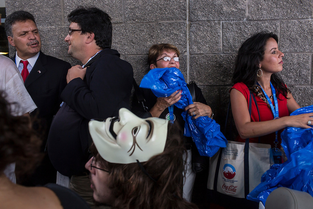 People take cover from a sudden rainstorm outside the Democratic National Convention on Tuesday, September 4, 2012 in Charlotte, NC.