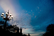 The top of the San Remo Building towers and the lightened fountain in Central Park at sunset, Manhattan, New York.