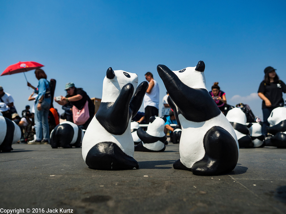 """04 MARCH 2016 - BANGKOK, THAILAND: People walk around paper maché pandas at the  opening of the """"1600 Pandas+ World Tour in Thailand: For the World We Live In and the Ones We Love"""" exhibit in Bangkok. The 1600 paper maché pandas, an art installation by French artist Paulo Grangeon will travel across Bangkok and parts of central Thailand for the next week and then will be displayed at Central Embassy, a Bangkok shopping mall, until April 10. The display of pandas in Thailand is benefitting World Wide Fund for Nature - Thailand and is sponsored by Central Embassy with assistance from the Tourism Authority of Thailand and Bangkok Metropolitan Administration and curated by AllRightsReserved Ltd.     PHOTO BY JACK KURTZ"""