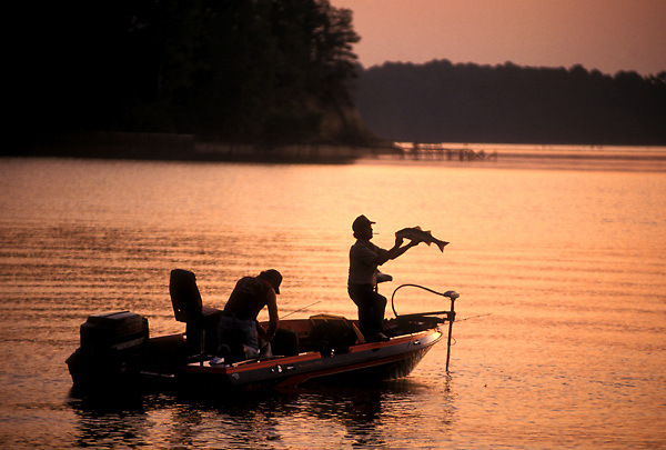 Stock photo of the silhouette of two men in a fishing boat on a lake at sunset