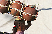 Young woman carrying the water pots on heads during market in Oecussi. @ Martine Perret. 12 September 2007