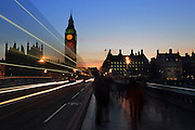 Light trails from a bus reflect the setting sun on Westminster Bridge in London