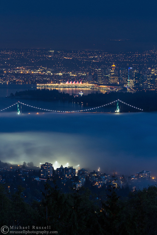 View of West Vancouver, Lions Gate Bridge, Stanley Park and downtown Vancouver as the fog rolls in from English Bay to Burrard Inlet.  Photographed from the Cypress Lookout at Cypress Provincial Park in West Vancouver, British Columbia, Canada