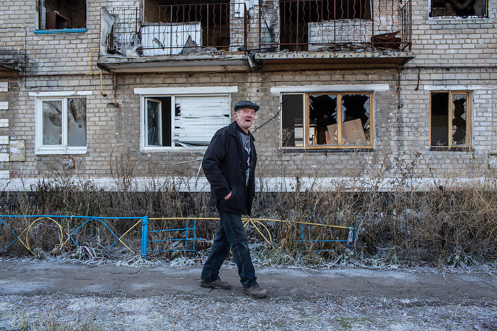 A local resident walks past a destroyed building to receive free bread delivered by the Good Word Protestant Church in need on Thursday, December 10, 2015 in Mariinka, Ukraine.