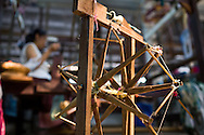 Threading a skein or bobbin winder. Ms.Cassidy's shop makes all threads 'in house'.