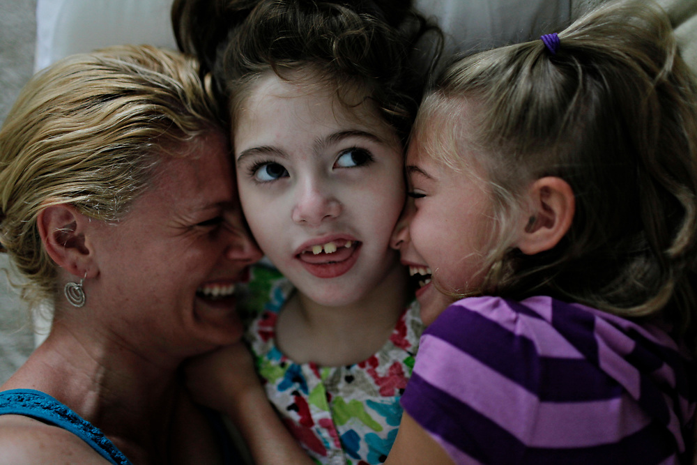 MELISSA LYTTLE       Times<br /> SP_351237_LYTT_TWINS_3 (June 8, 2012, Clearwater, Fla.) An afternoon snuggle break on the couch turns into a case of the giggles for Allison Scheinman and her seven-year-old twins Olivia, center, and Hailey. &quot;There's always something to smile about with these two,&quot; said Allison, who believes having a daughter with disabilities has helped her and her husband Jon find hope and joy in the small things. [MELISSA LYTTLE, Times]