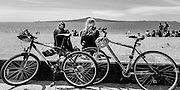 Two bikes, two women over looking beach, Rangitoto Island beyond, Mission Bay, Tamaki Drive, Auckland, New Zealand.