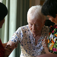 Healthcare workers help an Alzheimer's patient  walk at a live-in residence for Alzheimer's and dementia related  patients.
