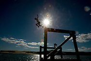 12-year-old Levi Parsons jumps of the Opononi wharf into the Hokianga Harbour, New Zealand. November 2005.<br />