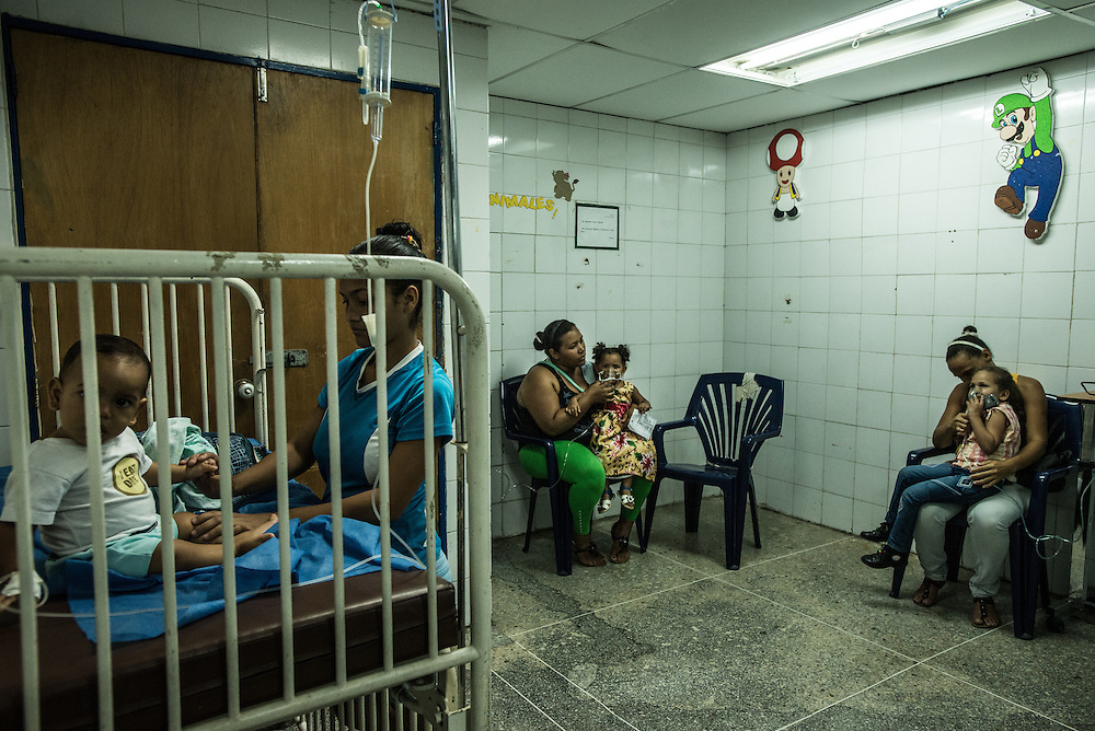 CATIA LA MAR, VENEZUELA - APRIL 12, 2016: Mothers give their children breathing treatments in the pediatric emergency room of a government-run clinic in Catia La Mar. Doctors here say they regularly have to turn patients away, because they don't have the majority of medicines  or medical equipment and supplies needed to give them medical attention.  When they do accept patients, they have to work with extremely limited resources. They said they regularly run out of medicines and supplies such as IV fluids, high-blood pressure medicine, baby asprin and masks. Despite having the largest oil reserves in the world, falling oil prices and wide-spread government corruption have pushed Venezuela into an economic crisis, with the highest inflation in the world and chronic shortages of food and medical supplies.   PHOTO: Meridith Kohut for The New York Times