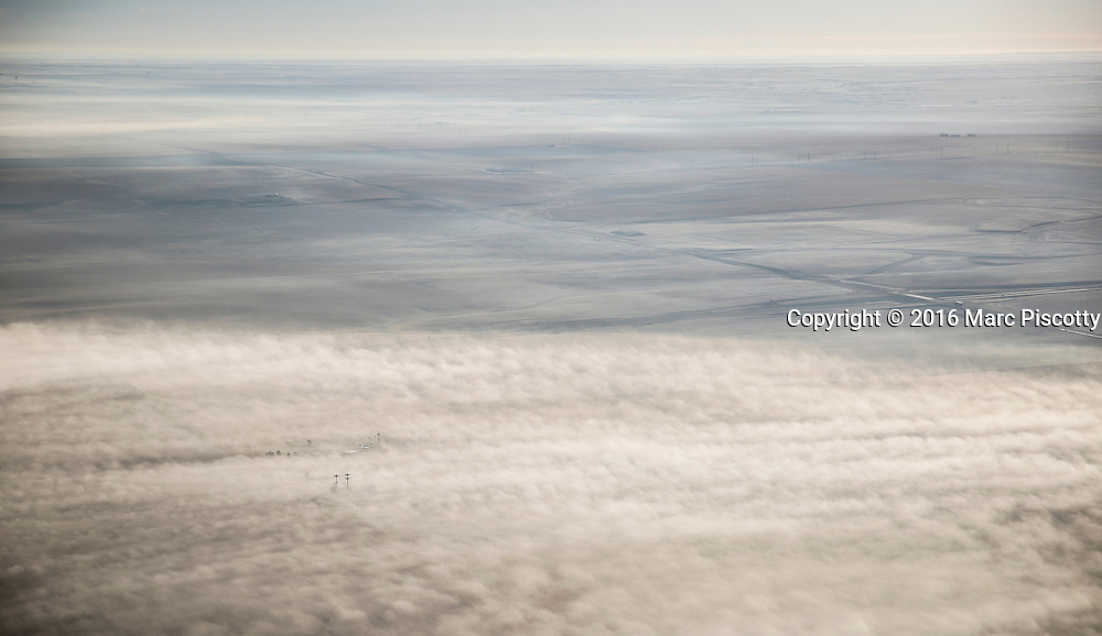 SHOT 12/3/16 9:11:46 AM - A pair of cell phone towers in the early morning fog on the plains of Colorado near Denver International Airport. As seen on a commercial flight headed from Denver, Co. to Cancun, Mexico. (Photo by Marc Piscotty / © 2016)