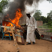 A man stands near a vehicle and other belongings set on fire by its owners who did not want to leave them behind for looters as Muslim families prepare to be evacuated by road, with the help of an armed convoy escorted by African Union peacekeepers, near the PK 12 neighbourhood in Bangui.