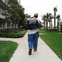 PALM BEACH, LA - September 5, 2005: .Chaney family enjoy their first morning outside the ravaged New Orleans at the complex housing them in Palm Beach, Florida on Sept 5, 20006. They wanted to read newspapers and catch up on the news and find new clothes....Members of the Chaney family, Kenneth (large man with Laker jersey), Anthony (other man with white t shirt), Elaine (flower dress and hat), and Julia (woman with blue dress, hat and glasses--she's Ken's and Anthony's mother). Joseph (older man using cane to walk) and Velma (white ball cap). Joseph and Velma are Elaine's parents...... (Last name TK--check with reporter ken lee)..