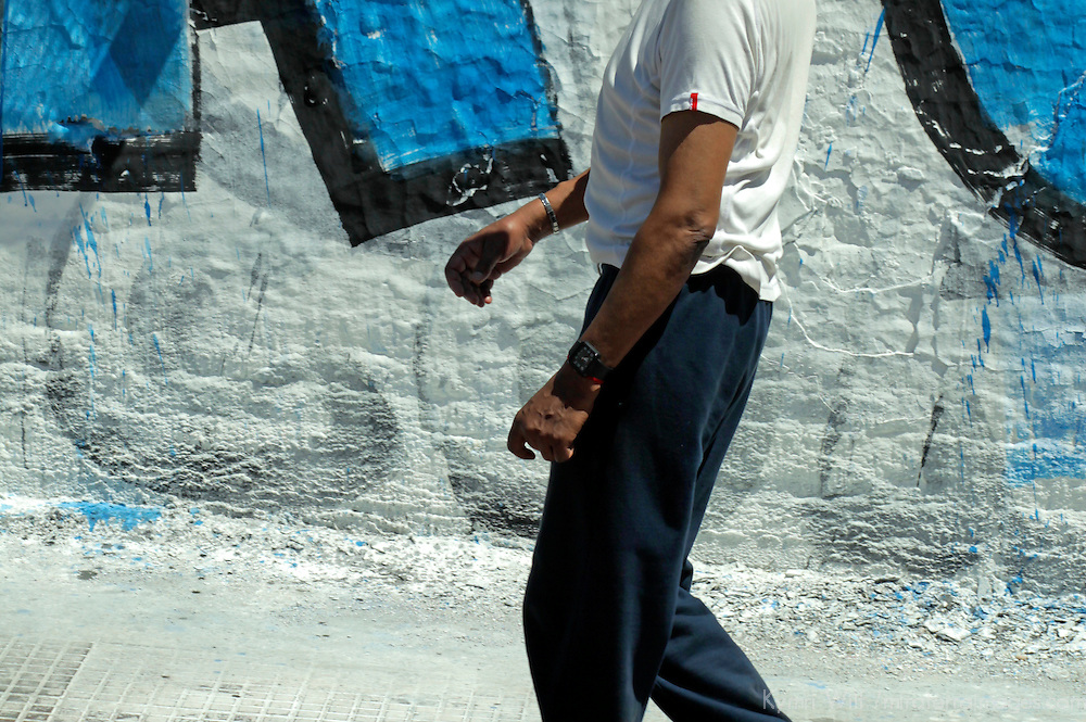 South America, Argentina, Buenos Aires. Man walking against wall of graffiti.