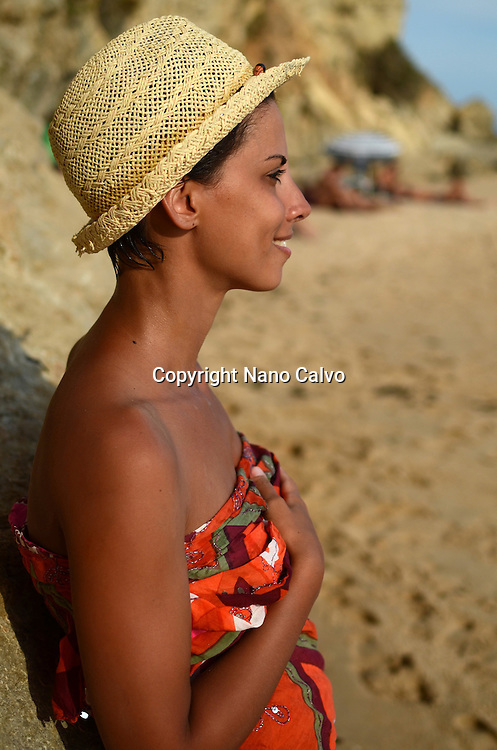 Young cute woman on the beach at sunset