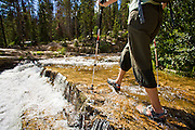 Trindl Nebeker uses trekking poles to steady herself as she wades across the Provo River in Utah's Uinta Mountains.
