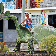 """A girl rides a tortoise sculpture in Puerto Baquerizo Moreno, on Isla San Cristóbal (Chatham Island), which is the easternmost island in the Galápagos archipelago, and one of the oldest geologically. Ecuador, South America. The Galápagos giant tortoise (Chelonoidis nigra, formerly called Geochelone elephantopus) can grow a shell up to about 5 feet (1.5 meters) long (smaller than this supersized sculpture). Published in """"Light Travel: Photography on the Go"""" book by Tom Dempsey 2009, 2010."""