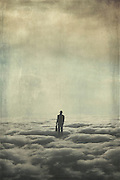 Business man standing knee deep in cloud looking into the distance - surreal photo manipulation