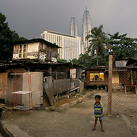 Malaysia, Kuala Lumpur..Architecture. Poverty. Contrast. The Petronas Twin Towers, a luxury hotel (Radisson) and slum housing...©Mark Henley