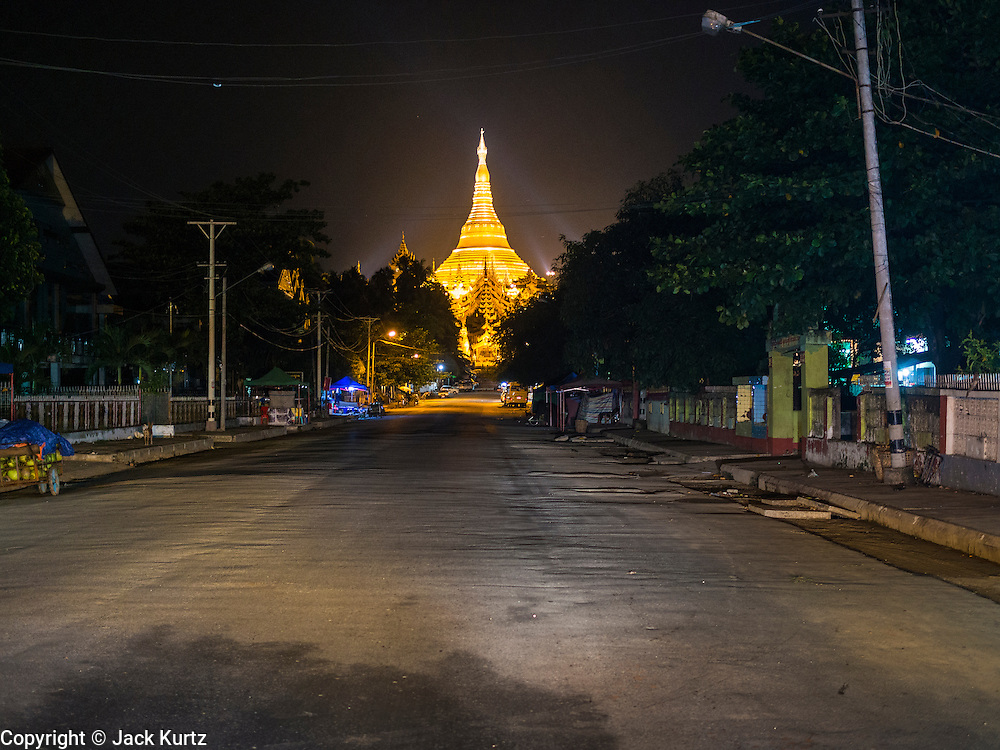 07 JUNE 2014 - YANGON, YANGON REGION, MYANMAR: Shwedagon Pagoda lit up at night in Yangon (Rangoon), Myanmar (Burma). Shwedagon Pagoda is officially called Shwedagon Zedi Daw and is also known as the Great Dagon Pagoda and the Golden Pagoda. It's a 99 metres (325ft) gilded pagoda and stupa located in Yangon. It is the most sacred Buddhist pagoda in Myanmar with relics of the past four Buddhas enshrined within: the staff of Kakusandha, the water filter of Koṇāgamana, a piece of the robe of Kassapa and eight strands of hair from Gautama, the historical Buddha.   PHOTO BY JACK KURTZ