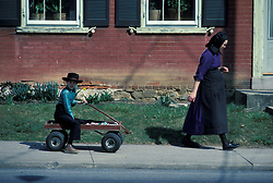 Young amish woman and son follwing in his little red wagon. Lancaster county, PA.