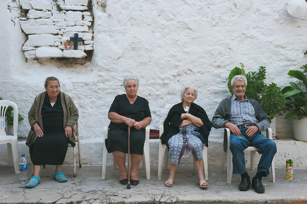 Elderly people sitting by the side of the alley inside the castle of Chios.