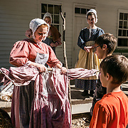 Young women in 1800s costume design a scarecrow. Conner Prairie Interactive History Park, Fishers, Indiana, USA. Conner Prairie provides family-friendly fun for all ages. Founded by pharmaceutical executive Eli Lilly in the 1930s, Conner Prairie living history museum now recreates life in Indiana in the 1800s on the White River and preserves the William Conner home (listed on the National Register of Historic Places). For licensing options, please inquire.