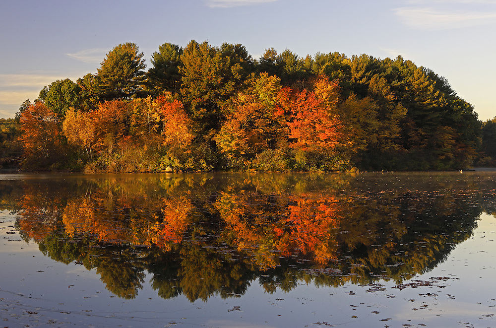Massachusetts Route 9 is a vital artery for travelers and commuters to get in and out of Boston. It also provides great opportunities to experience the New England fall foliage. This autumn image was taken shortly after sunrise in the Town of Southborough. The solitude of early morning, when the sun paints the fall foliage in warm hues, is my preferred time to explore magic of Mother Earth. Nearby Southborough in Worcester County with it&rsquo;s beautiful lakes makes for quick outings and beautiful viewing of colorful fall foliage. Last week autumn colors were peaking which made for a perfect autumn scenery and fall foliage reflection.  <br />