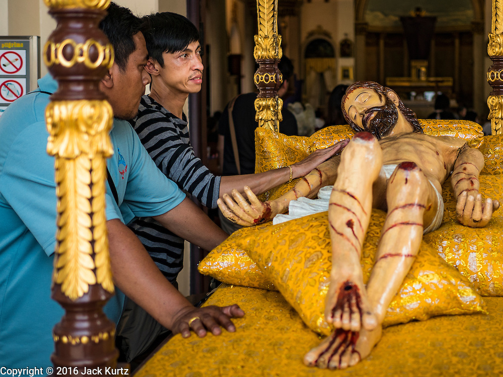 25 MARCH 2016 - BANGKOK, THAILAND: Men pray at a statue of Jesus during Good Friday observances at Santa Cruz Church in Bangkok. Santa Cruz was one of the first Catholic churches established in Bangkok. It was built in the late 1700s by Portuguese soldiers allied with King Taksin the Great in his battles against the Burmese who invaded Thailand (then Siam). There are about 300,000 Catholics in Thailand, in 10 dioceses with 436 parishes. Good Friday marks the day Jesus Christ was crucified by the Romans and is one of the most important days in Catholicism and Christianity.      PHOTO BY JACK KURTZ