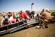 Rescue workers and crewmembers work to free Dennis Reick from his destroyed car at the National Sand Drad Race Association's 2009 Summer Nationals in Avenal, CA May 17, 2009.