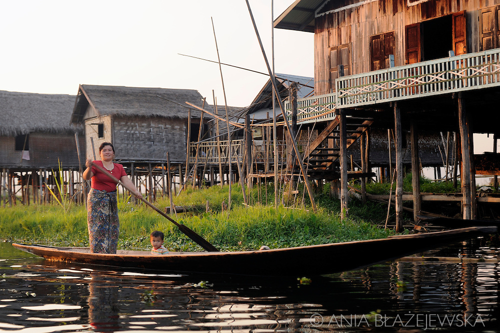 Myanmar/Burma, Maing Thauk. Woman paddling the boat near her house in Maing Thauk, one of the Intha villages situated at the Inle Lake.<br /> Maing Thauk is a special village because half of it is set on dry land, while the other half sits on stilts over the water, linked to the shore by a wooden bridge.