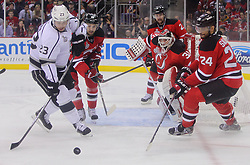 May 30; Newark, NJ, USA; New Jersey Devils defenseman Bryce Salvador (24) and Los Angeles Kings right wing Dustin Brown (23) chase a loose puck after a save by New Jersey Devils goalie Martin Brodeur (30) during the first period of 2012 Stanley Cup Finals Game 1 at the Prudential Center.  The Kings defeated the Devils 2-1.