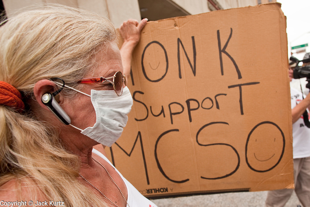 """19 JUNE 2009 -- PHOENIX, AZ: Sheriff's supporter Barb Heller (CQ) wore a breathing mask while demonstrating in favor of the Sheriff's sweeps FridayThe Sheriff's Department is headquartered in the Wells Fargo Bank building. Rev. Al Sharpton was in Phoenix Friday to protest the high profile """"crime suppression"""" sweeps conducted by the Sheriff's Department. Critics contend the sweeps use racial profiling to target Hispanics. PHOTO BY JACK KURTZ"""